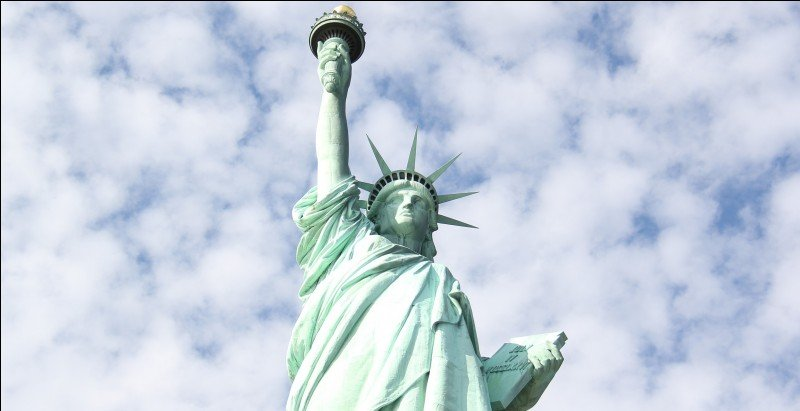 In which hand does Lady Liberty hold a stone tablet?