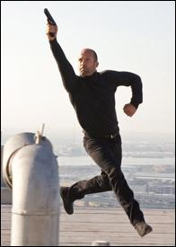 Jason Statham Holding a Gun and Running in...